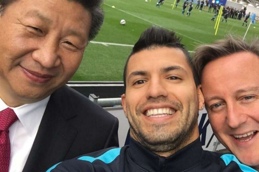 """Manchester City's Argentinian striker Sergio Aguero (centre) poses for a """"selfie""""  with Xi (left)  and British Prime Minister David Cameron during their visit to the City Football Academy."""