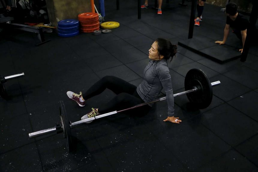 Kim Jin Ah, 31, rests as she takes part in a crossfit class at a gym in Seoul on Sept 11, 2015.