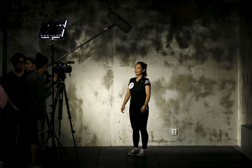 A participant is interviewed before the start of a workout session during the TV programme The Body Show at a gym in Seoul on Sept 19, 2015.