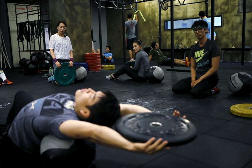 You Ri Seul (left), 29, and Kim Jin Ah (centre), 31, take part in a crossfit class at a gym in Seoul, on Sept 11, 2015.