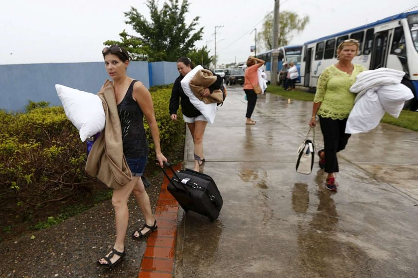 Tourists evacuated from their hotel arrive at the University of Puerto Vallarta, which is being used as a shelter as Hurricane Patricia approaches.