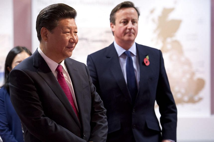 Chinese President Xi Jinping (left) and British Prime Minister David Cameron tour an exhibition of future developments in the north of England at Manchester Airport on Oct 23.