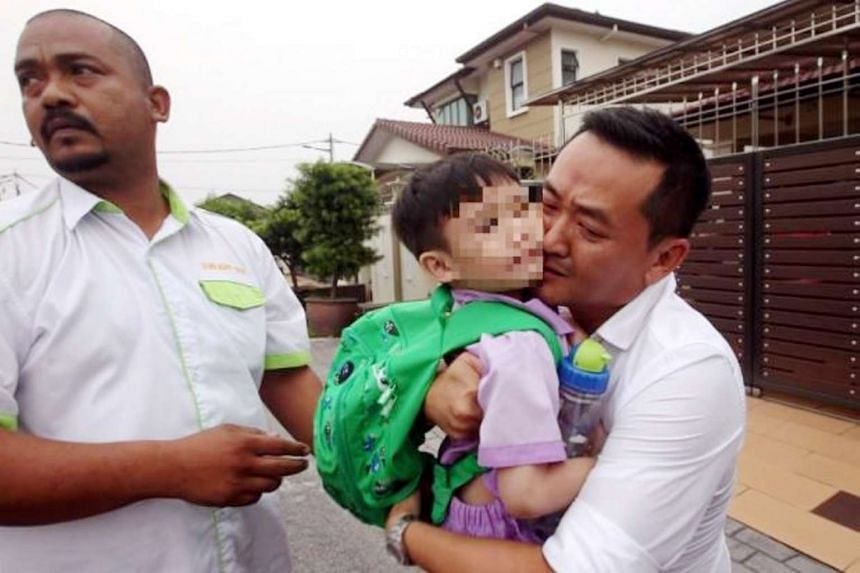 A five-year-old boy who was abducted in Jalan Cempaka, Kajang being returned to his family by a taxi driver, on Oct 9, 2015. Cab driver Hanizan Mohamed Radzi, 41, was arrested along with three other men over the kidnapping, but the police later clear