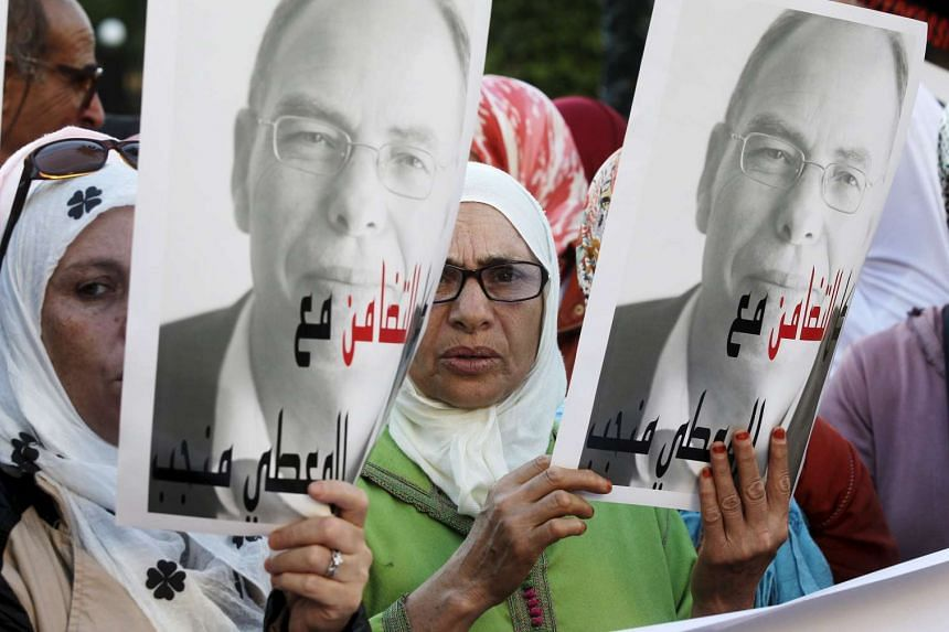 """Moroccan protesters hold up posters of Maati Monjib, a Moroccan professor of political history, to support him during a demonstration in the capital, Rabat, on Oct 21, 2015. The sign reads, """"Even if you use repression, your intimidation is useless""""."""