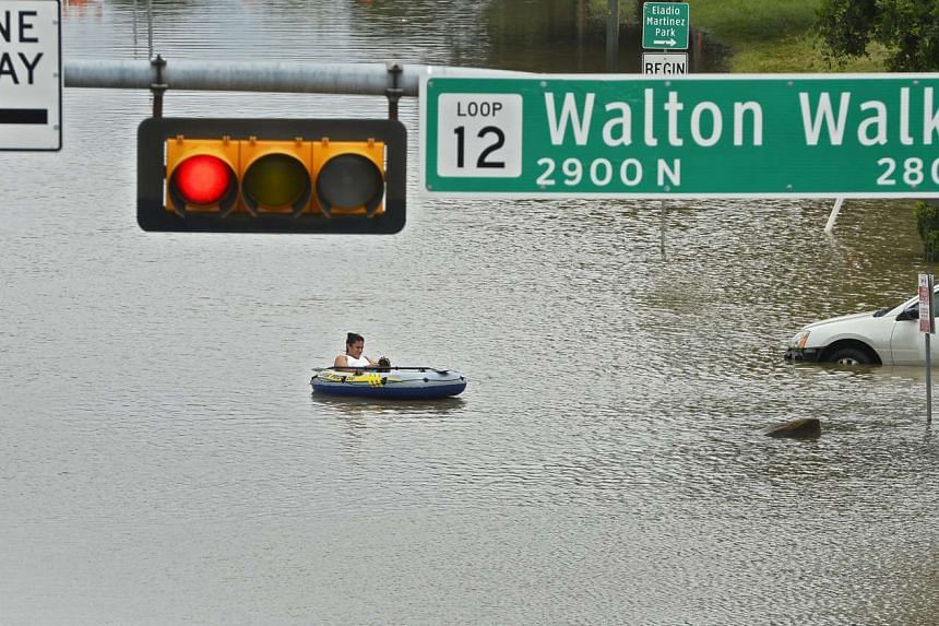 Beatrice Banda paddles a rubber raft through floodwater in Dallas, Texas, USA, on May 30, 2015.