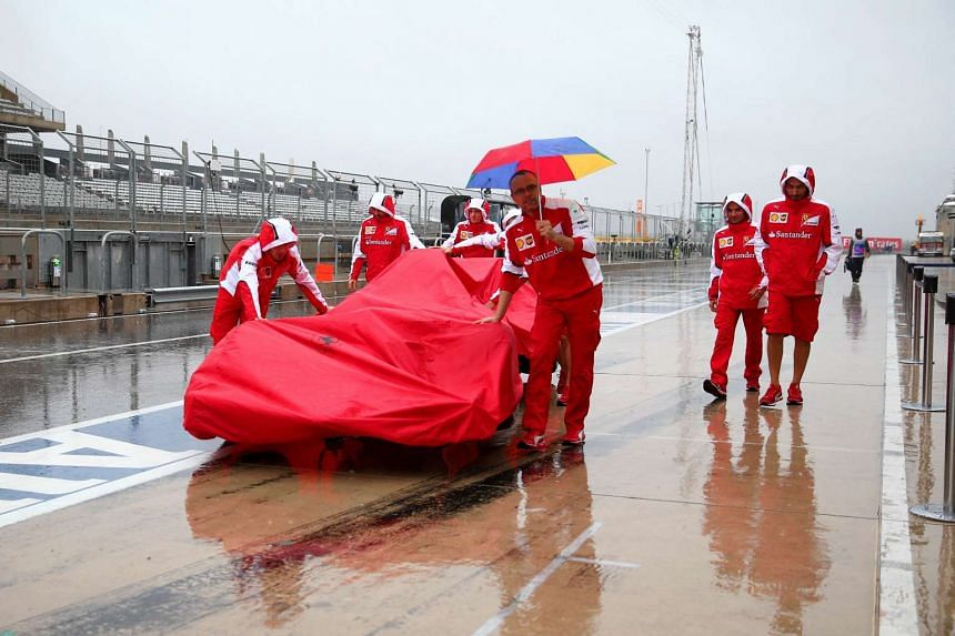 Members of the Ferrari team push a car down the pit lane as heavy rain falls before final practice for the United States Formula One Grand Prix at Circuit of The Americas on Oct 24, 2015 in Austin, United States.