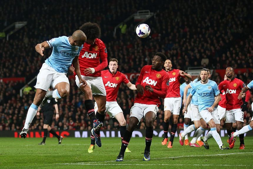 Manchester United's Marouane Fellaini in action against Manchester City's Vincent Kompany during the Barclays Premier League football match in 2014.