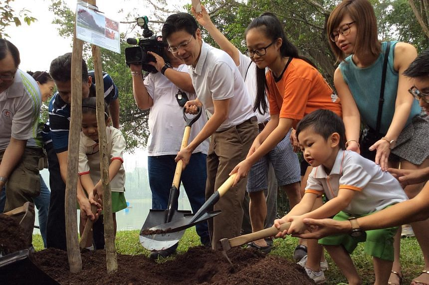 National Development Minister Lawrence Wong planting trees at Jurong Lake Park, which will eventually become Jurong Lake Gardens West.