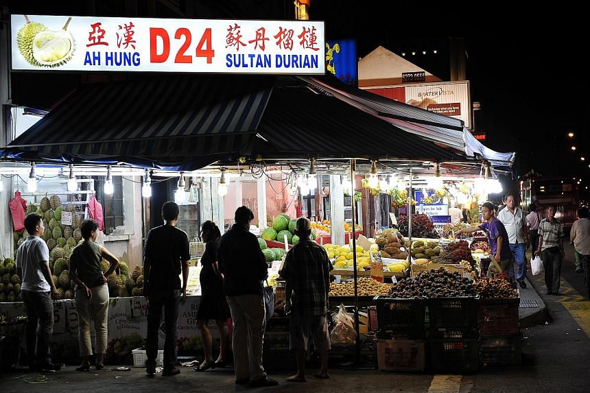 Lining the streets of Geylang are brightly lit fruit shops (above) that offer a unique experience of eating by the roadside, with cars zooming past. Eminent Frog Porridge (below), located in Geylang Lorong 19, is among the many culinary delights the