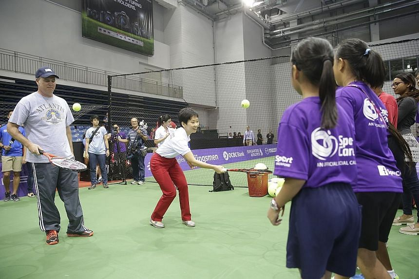 US ambassador to Singapore Kirk Wagar (left) and Minister for Culture, Community and Youth Grace Fu juggle tennis balls during SportCares' Love Singapore tennis clinic. SportCares will launch a wheelchair tennis project for underprivileged youth and
