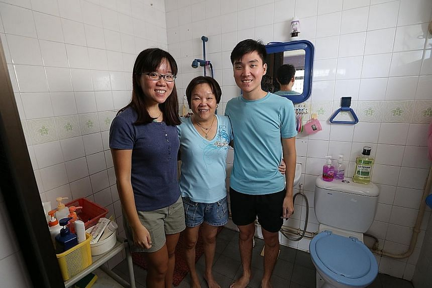 (From left) Teacher Jasmine See, winner of the ST170 Treats bathroom makeover, with her mother Joyce Chiang and brother Nicholas in their HDB bathroom which has not been renovated in about 20 years.