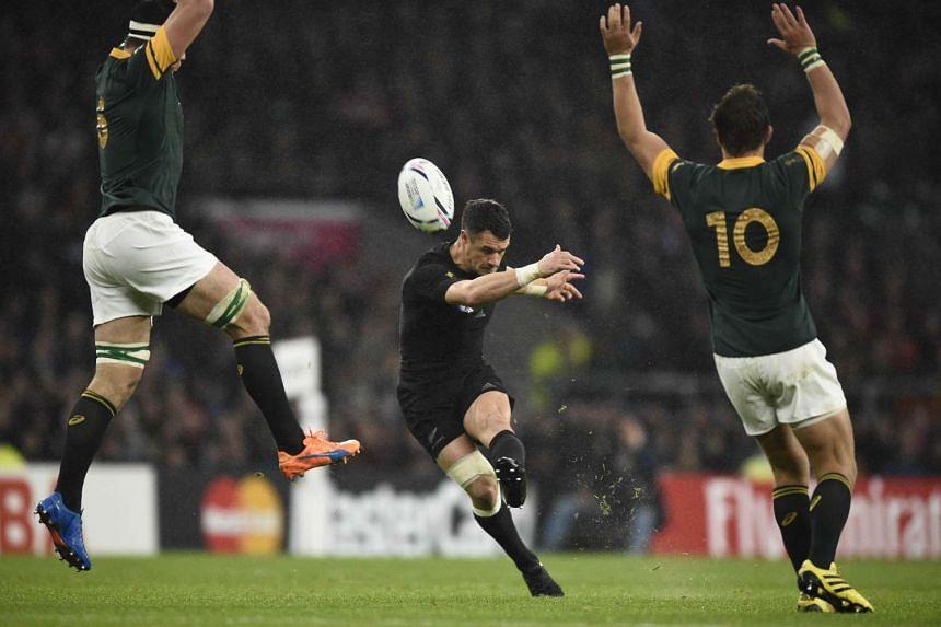 New Zealand's fly half Dan Carter kicks and scores a drop goal.