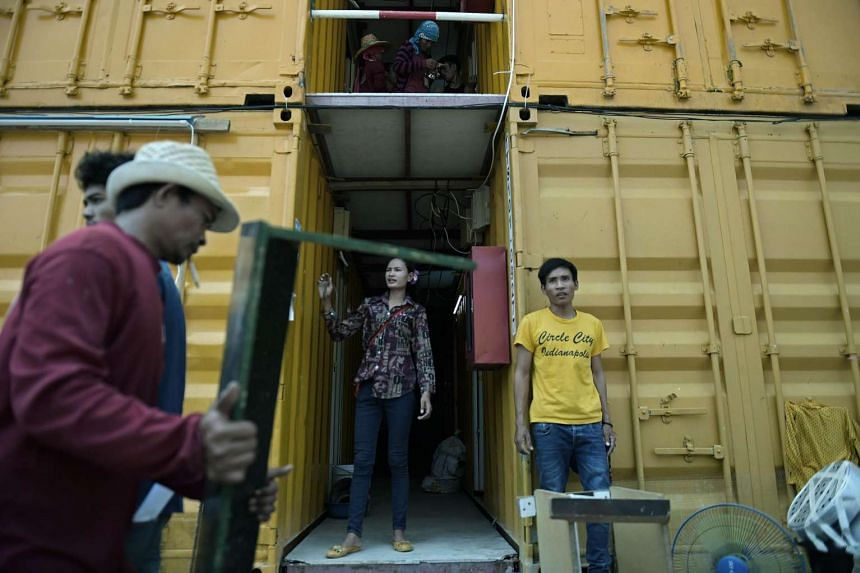 This picture taken on Sept 21, 2015 shows a man (L) carrying a piece of furniture as workers move in at a construction workers' camp made of steel containers in Samut Prakan, greater Bangkok. On the outskirts of Bangkok, rows of yellow containers pil