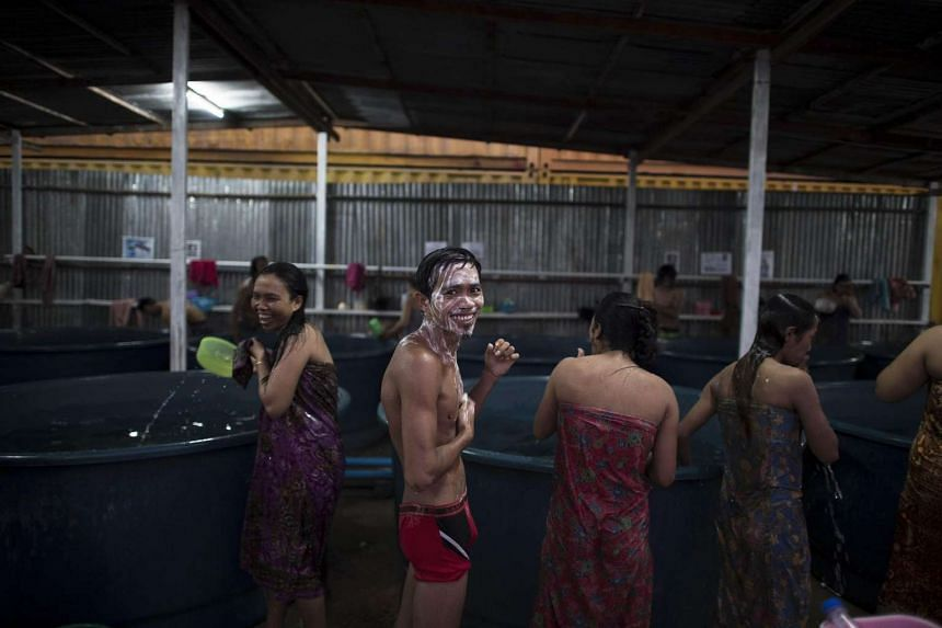 This picture taken on Oct 8, 2015 shows men and women having a shower at a washing area at a construction workers' camp made of steel containers in Samut Prakan, greater Bangkok. On the outskirts of Bangkok, rows of yellow containers piled onto each