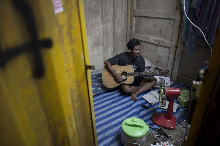 This picture taken on Oct 1, 2015 shows Laotian worker Hussadee Sriphrajun, 30, playing the guitar at his housing unit at a construction workers' camp made of steel containers in Samut Prakan, greater Bangkok. On the outskirts of Bangkok, rows of yel