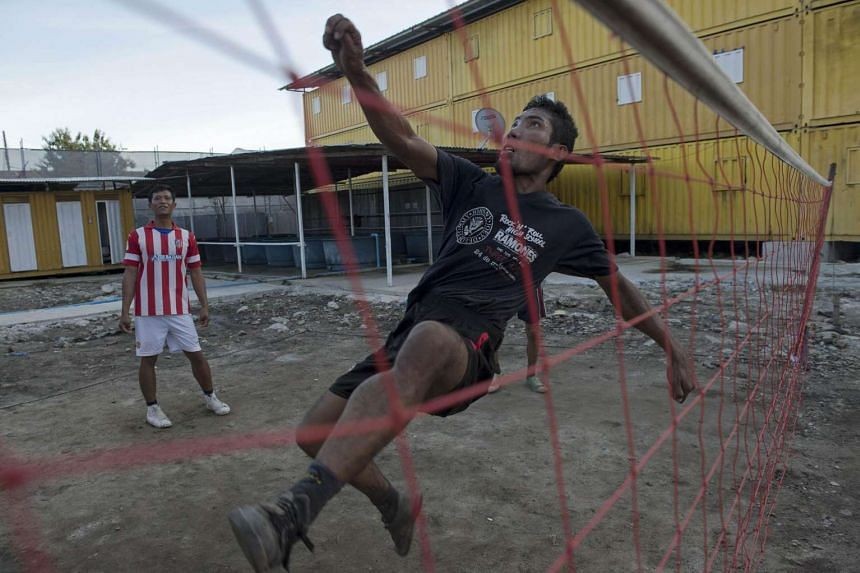 This picture taken on Sept 24, 2015 shows Laotian worker Hussadee Sriphrajun, 30, playing the traditional southeast Asian game of sepak takraw at a construction workers' camp made of steel containers in Samut Prakan, greater Bangkok. On the outskirts