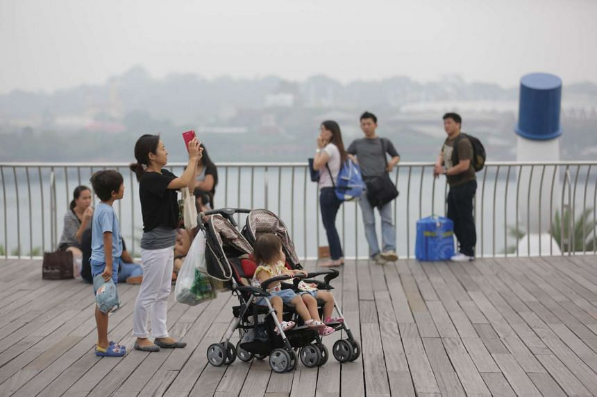 A woman taking a picture on her smartphone at VivoCity as haze covers Sentosa in the background, at about 5pm on Oct 25, 2015.