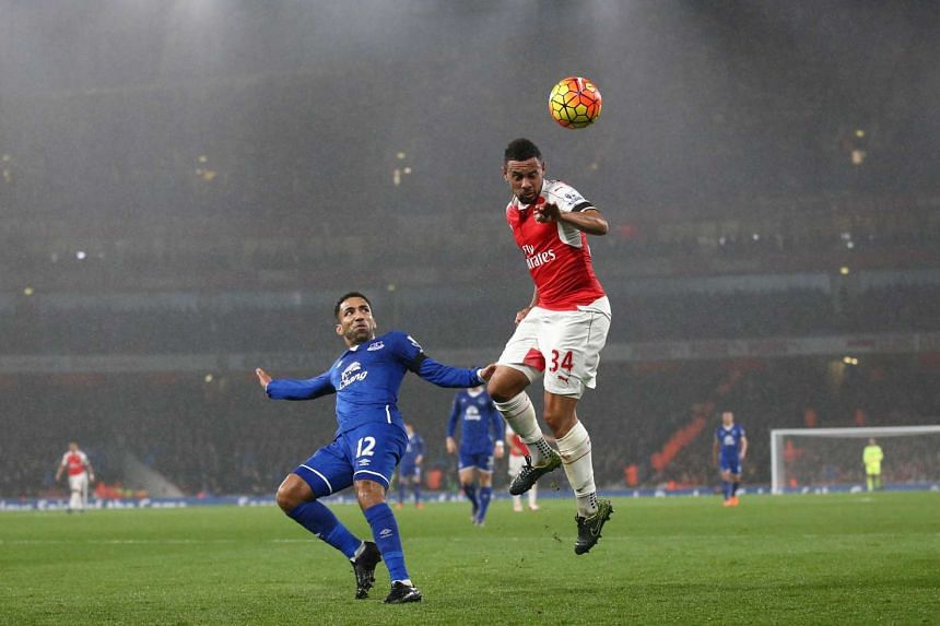 Arsenal's French midfielder Francis Coquelin (right) jumps to win a header as Everton midfielder Aaron Lennon (left) looks on.