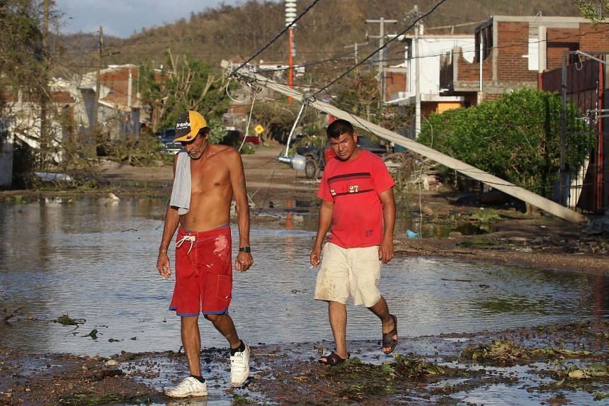 Men walk along a street following Hurricane Patricia's passage, in Francisco Villa, Jalisco, Mexico, on Oct 24, 2015. Heavy rainfall caused by the storm have hit parts of Texas as the US state prepares for flooding.