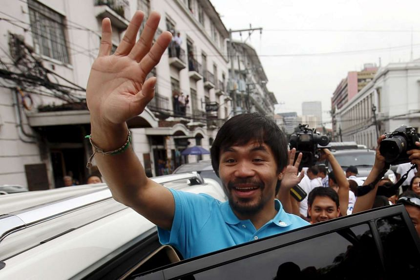 Filipino boxer Manny Pacquiao waving to supporters after filing his Certificate of Candidacy for Senator at the Commission on Elections in Manila, Philippines on Oct 16, 2015.