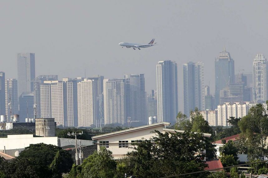 A Philippines Airlines plane prepares to land in Manila as haze from Indonesian forest fires shrouds the capital on Oct 25, 2015.