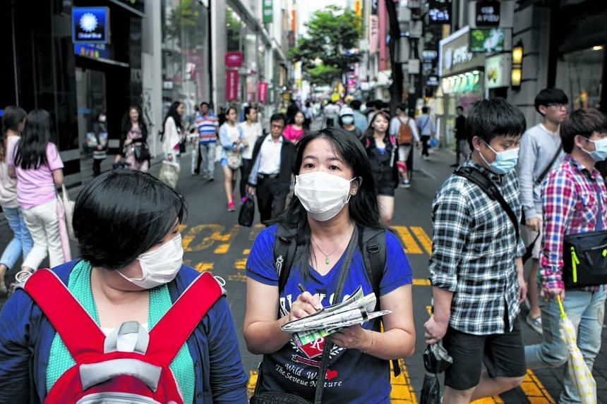 Chinese tourists wearing masks to prevent contracting Middle East Respiratory Syndrome (Mers) while shopping at Myeongdong shopping district in central Seoul on June 5, 2015, during the Mers outbreak.