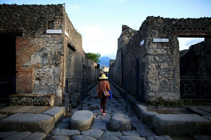 A tourist walks along an ancient Roman cobbled street at the Unesco World Heritage site of Pompeii on Oct 13, 2015.