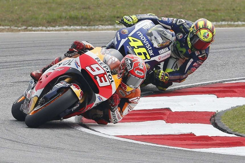 Honda MotoGP rider Marc Marquez (front) of Spain and Yamaha MotoGP rider Valentino Rossi of Italy ride during the Malaysian Motorcycle Grand Prix at Sepang International Circuit on Oct 25, 2015.