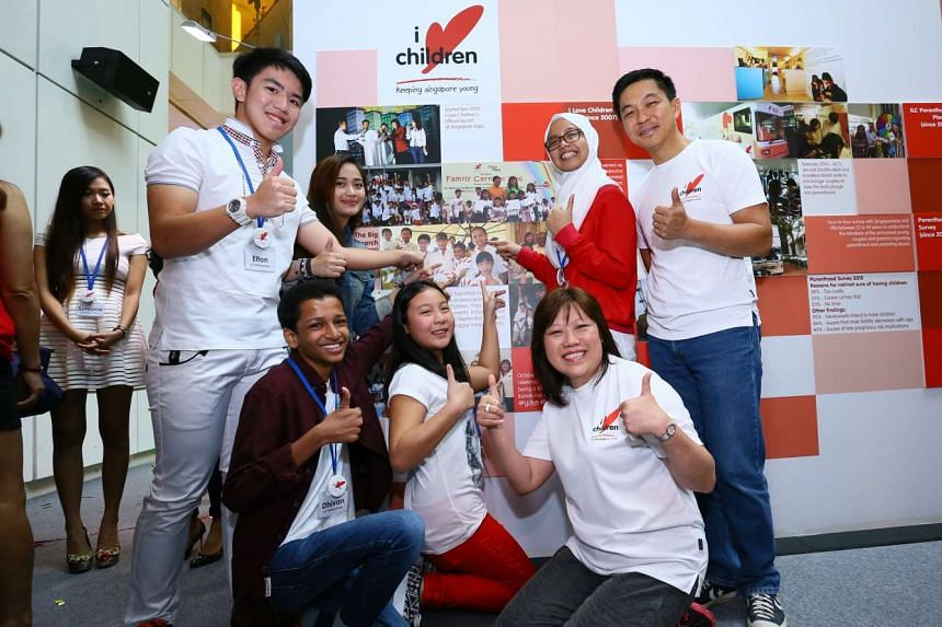 Minister for Social and Family Development Tan Chuan-Jin (standing, far right), who was the guest of honour at the I Love Children roadshow at United Square shopping mall yesterday, with the voluntary welfare organisation's president Joni Ong (kneeli