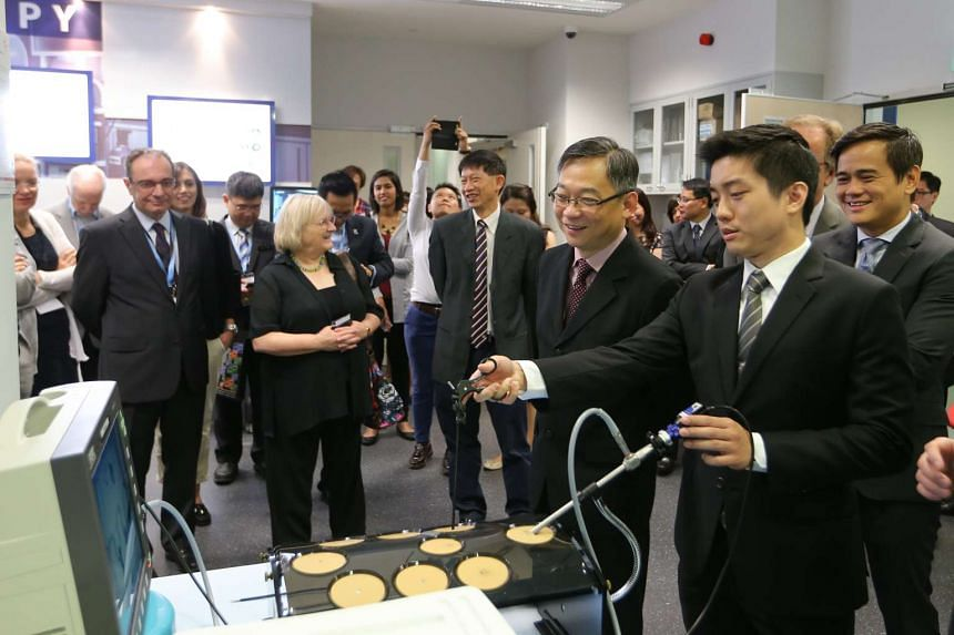 Health Minister Gan Kim Yong (second from right) observing how a laparoscopic simulator works at the SingHealth Duke-NUS Surgical Skills and Simulation Centre on the SGH campus yesterday.