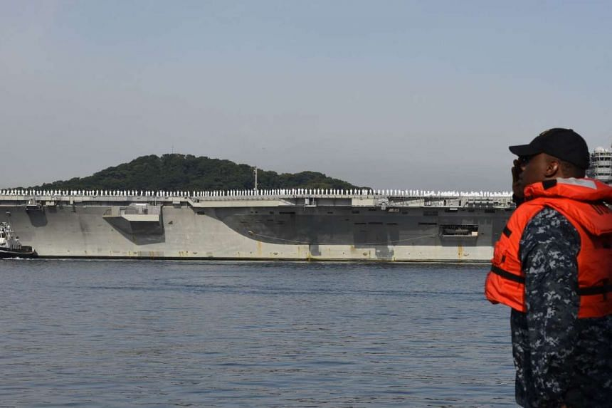 US soldiers salute as the aircraft carrier USS Ronald Reagan sails into the US Navy base in Yokosuka on Oct 1, 2015.