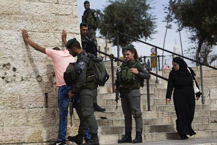 Israeli border policemen perform a security check on a Palestinian youth at the Damascus Gate just outside Jerusalem's Old City before Friday prayers on Oct 23, 2015.