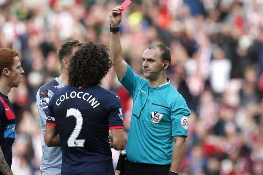 Referee Robert Madley handing Newcastle defender Fabricio Coloccini a red card during their English Premier League match against Sunderland at the Stadium of Light on Oct 25, 2015.