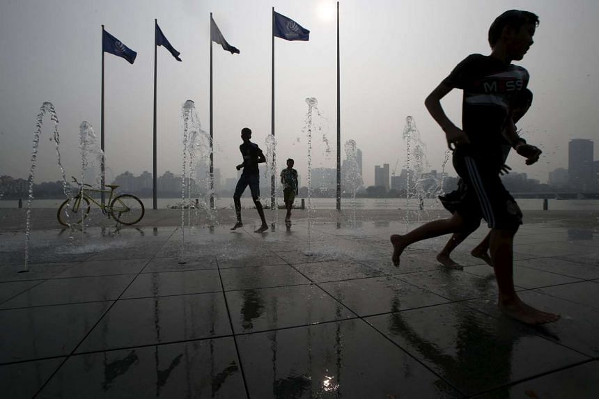 Children play at a water fountain on a warm day, against the backdrop of the city skyline shrouded by haze on October 26, 2015