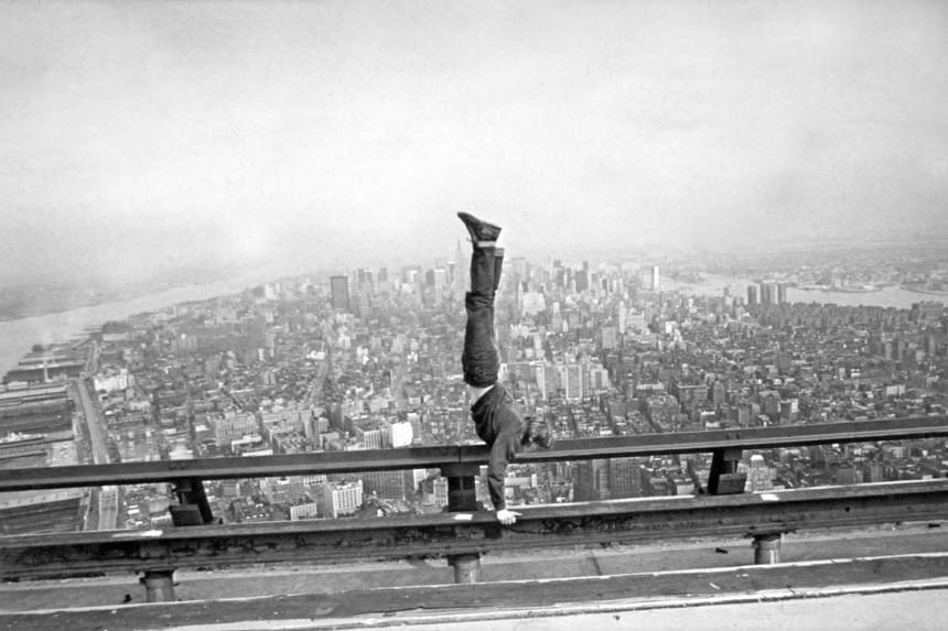 Philippe Petit warms up with a handstand as the New York skyline looms below him. He illegally rigged up a tightrope between the Twin Towers of the World Trade Center and then danced across it.