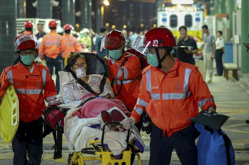 An injured ferry passenger is escorted by rescuers after getting onshore in Hong Kong, China on Oct 25, 2015.