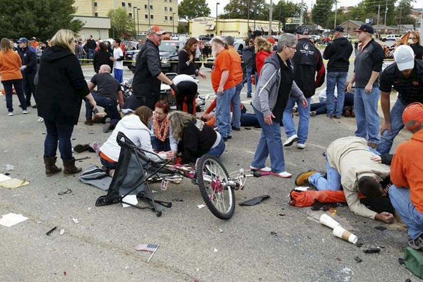 People helping the injured after a car drove into a homecoming parade at Oklahoma State University in Stillwater on Oct 24, 2015, in this handout photo provided by David Bitton/Stillwater News Press.