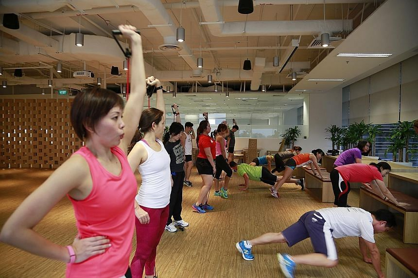 SAP employees, some wearing fitness trackers, exercising at the company's UFit bootcamp, which is held on Mondays.