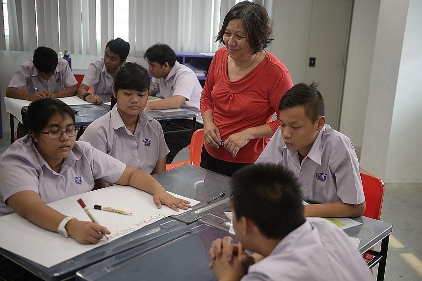 NorthLight Academy job coach Lim Peck Gee supervising students as they prepared a presentation on what they learnt after a visit to a fast-food joint last week.