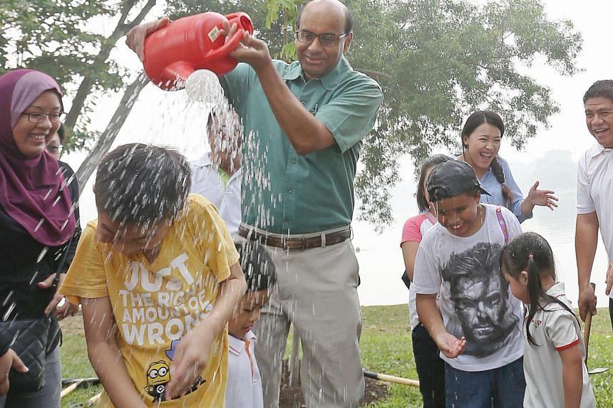 It wasn't just the trees at Jurong Lake Park that got a watering yesterday from Deputy Prime Minister Tharman Shanmugaratnam. After planting a Malayan crepe myrtle tree with others, Mr Tharman also gave Aw Jun Le, nine, a sprinkling of water.
