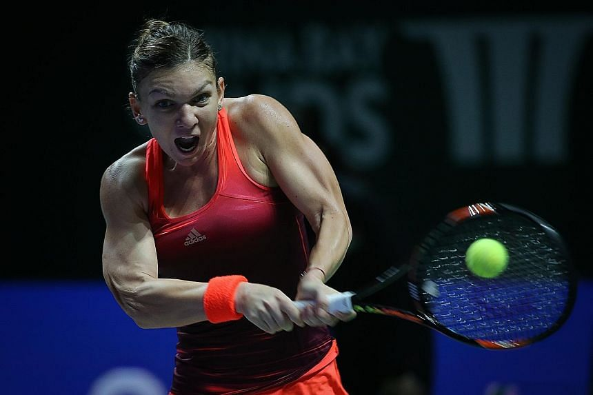 Simona Halep playing a backhand return to Flavia Pennetta in her 6-0, 6-3 win yesterday. The top seed in the WTA Finals aims to go one better than last year when she lost in the final to Serena Williams.