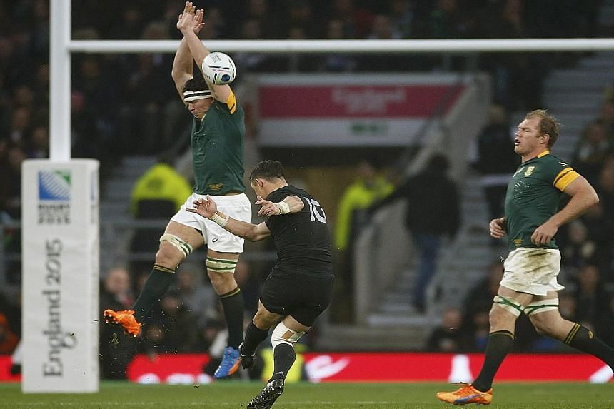 Above: All Blacks' first-five Dan Carter letting fly with a sweetly struck drop goal to help turn the momentum in Saturday's Rugby World Cup semi-final against South Africa. Right: Sonny Bill Williams (right) thanks the heavens after New Zealand win