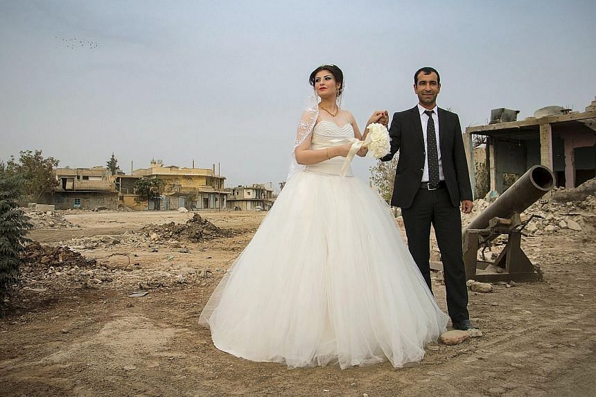 A Kurdish couple posing for a wedding shot in war-ravaged Kobani on Friday. The area is controlled by Kurdish-led forces. In the previous presidential election, Kurdish officials said they would not allow the Assad regime to open polling stations in