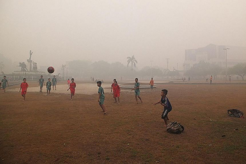 Left: Children playing football at a Bundaran Besar field yesterday morning when the PSI level was around 1,500 in Palangkaraya, Central Kalimantan. Below: People at VivoCity in Singapore enjoying the outdoors at 5pm, when the 24-hour PSI reading was