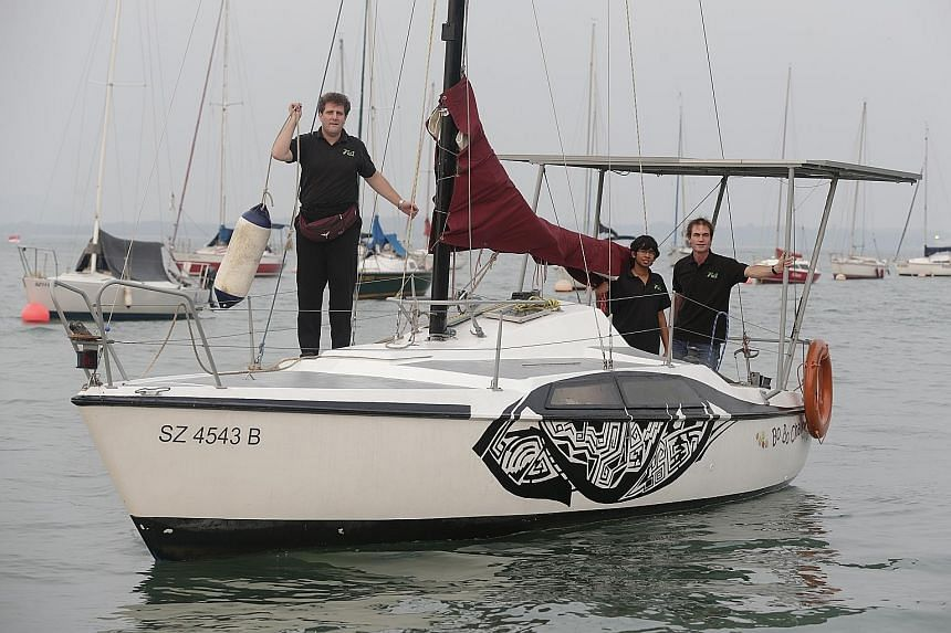 (From left) Dr Joerg Weigl, Mr Anand Sundaram and Associate Professor Martin Henz on board the Bo Bo Cha Cha at Changi Sailing Club. Without using its sail, the zero-carbon boat can travel for five hours non-stop, with a full speed of 5 knots, or abo