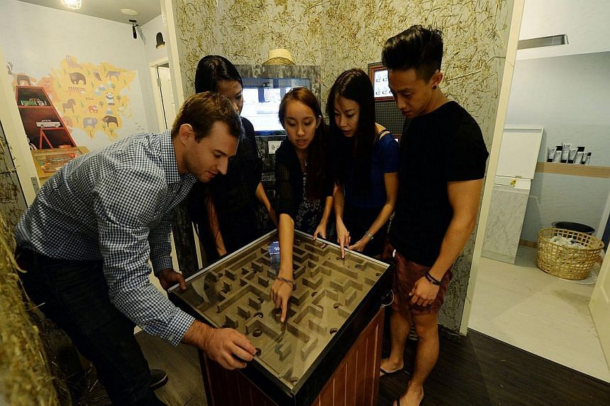 Players in a replayable escape game which was launched over a month ago at Lockdown Singapore. To sustain customers' interest, escape game companies here are improving their game rooms or adding new ones.