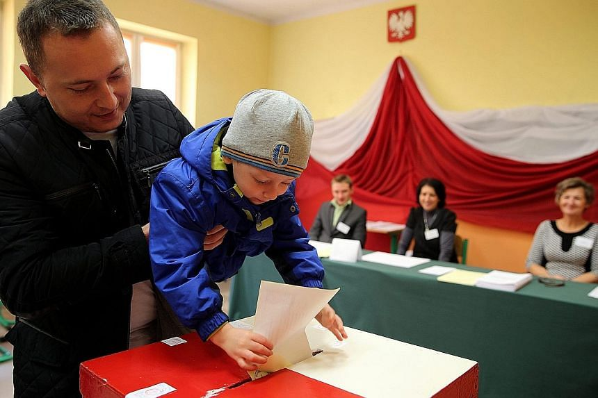A man letting his child drop his vote in a ballot box at a polling station in Przecieszyn, south Poland, yesterday.