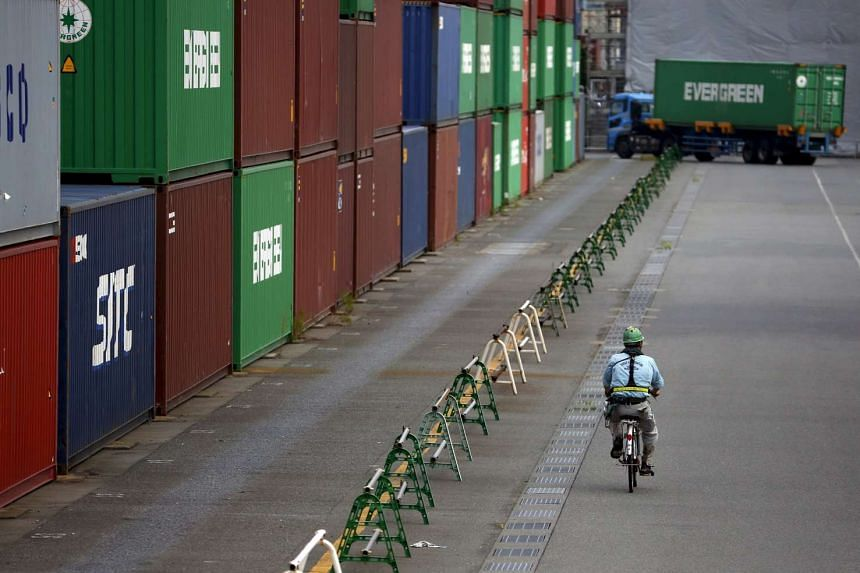 A worker rides a bicycle past containers at a port in Tokyo in this Aug 19, 2015.