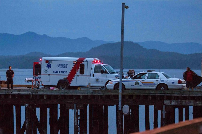 Rescue personnel mounting a search for victims of a capsized whale watching boat on a wharf in Tofino, British Columbia.