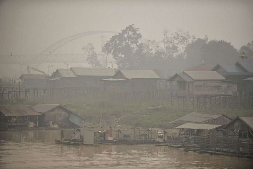 Residents living by the Kahayan riverbanks, go about their daily routines amid the haze, in Palangkaraya city, in Central Kalimantan, on Oct 25, 2015.